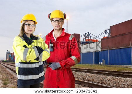 Two rail transport transit guards, posing in front of a container lot along rail tracks - stock photo