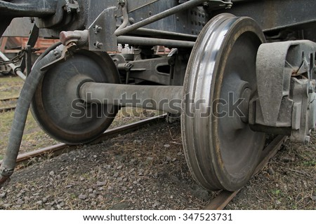 Two railroad car wheels on the rails closeup. The rear part of the cargo wagon