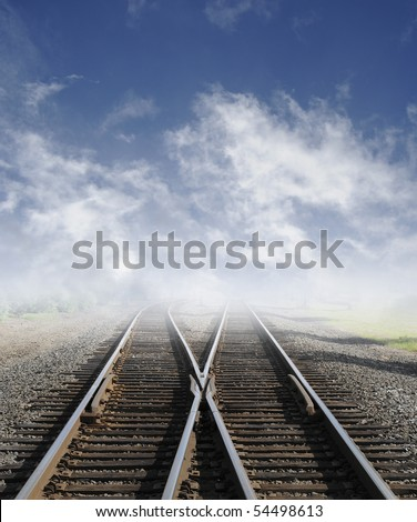 Two railroad tracks lead off into the daylight foggy sky with clouds. - stock photo