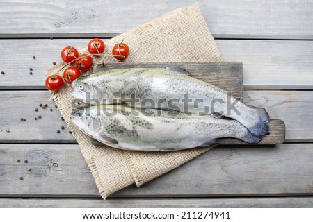 Two rainbow trouts and tomatoes on rustic wooden table - stock photo