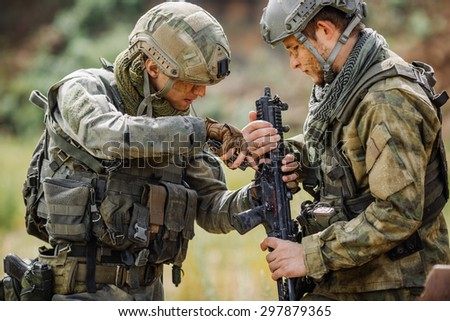 Two rangers repair fix the rifle with the tool in the battlefield - stock photo