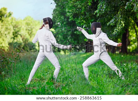 Two rapier fencer women fighting over beautiful nature background - stock photo