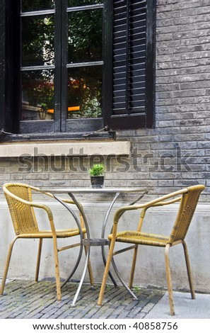 Two rattan cafe chairs against brick wall of a restaurant - stock photo