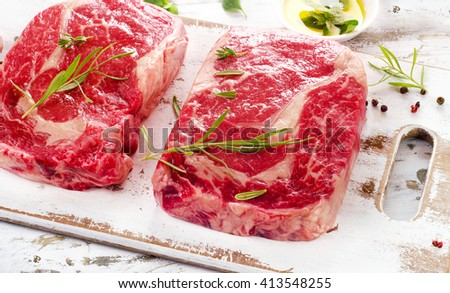 Two Raw Beef Steaks on a white wooden  background. - stock photo