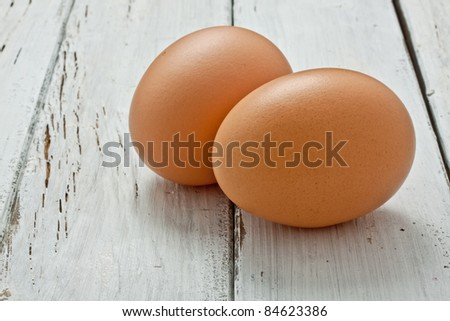 two raw eggs on a wood table - stock photo