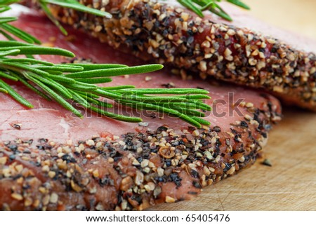 Two raw, eye of round, Alberta beef steaks, encrusted with pepper & spices and topped with fresh rosemary.  BBQ ready!  Shallow depth of field. - stock photo
