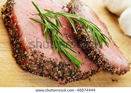Two raw, eye of round, Alberta beef steaks, with pepper & spices and topped with fresh rosemary. - stock photo