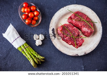 Two raw fillet steaks with green asparagus, mushrooms, cherry tomatoes with a slate background