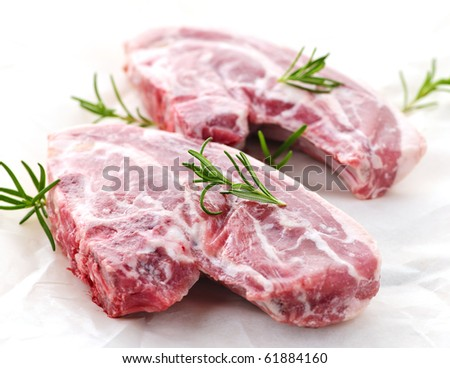 Two raw fresh lamb chops with rosemary herb - stock photo