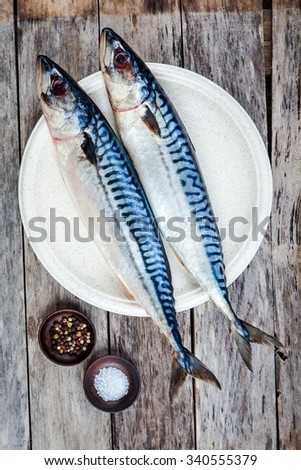 Two raw fresh mackerel fishes on a plate with salt and pepper on wooden table - stock photo