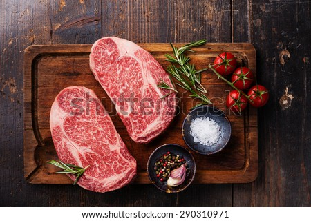 Two Raw fresh marbled meat Black Angus Steak Ribeye and seasonings on dark wooden background  - stock photo