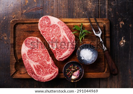 Two Raw fresh marbled meat Black Angus Steak Ribeye, seasonings and meat fork on dark wooden background  - stock photo