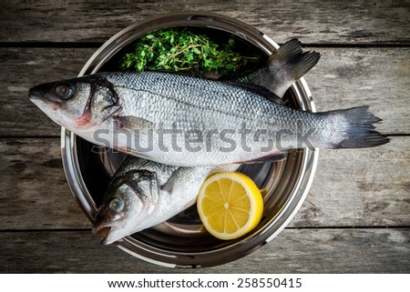 two raw fresh sea bass in a bowl with thyme and lemon on wooden table - stock photo
