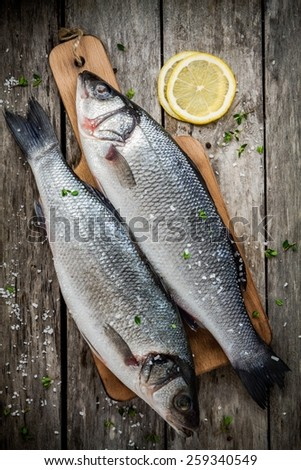 two raw fresh sea bass on a cutting board with lemon and sea salt on wooden rustic table - stock photo