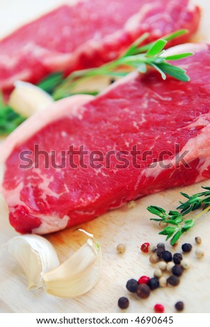 Two raw new york steaks on cutting board with thyme peppercorns and garlic - stock photo