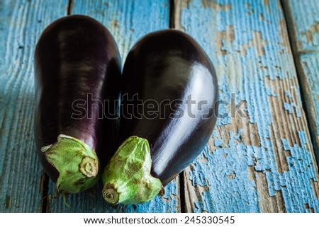 Two raw organic eggplant on old rustic wooden background - stock photo