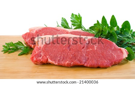 Two raw porterhouse steaks on a wooden chopping board with herbs - stock photo