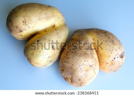 Two raw potatoes looking like a hearts - stock photo