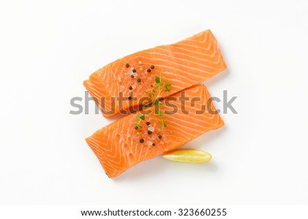 two raw salmon fillets with spice on white background