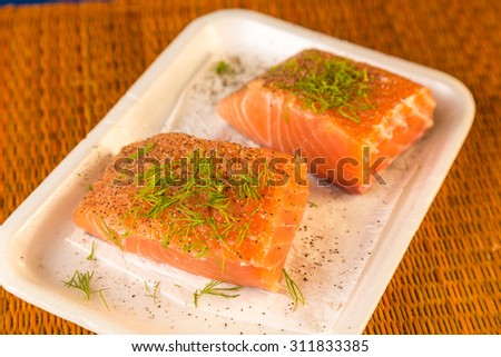 Two raw  salmon steaks still in styrofoam tray being seasoned and prepared for cooking.  Closeup with selective focus and  shallow dof. - stock photo