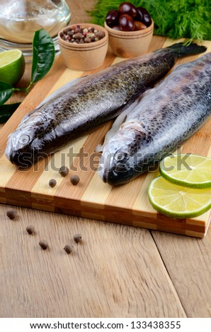 Two raw trout set on the chopping board with lime and spices - stock photo