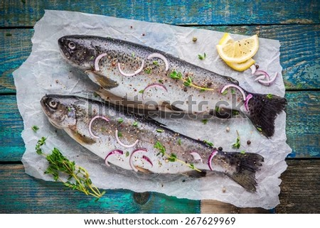 two raw trouts on paper with thyme and lemon and red onion slices on a rustic wooden table - stock photo