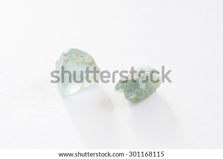 Two raw unpolished aquamarine gemstones. They are translucent with a light blue/cyan color - stock photo