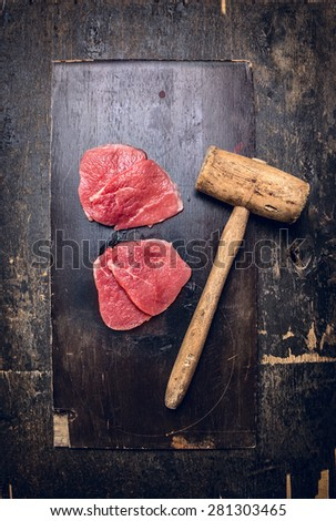 Two raw  veal meat schnitzel  with old meat hammer on dark rustic background, top view - stock photo