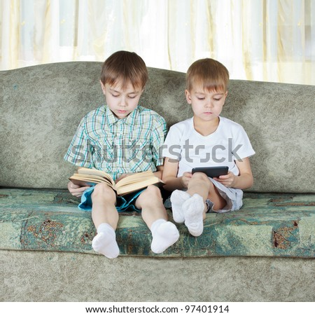 Two reading boys at sofa. One with paper book, other with electronic book - stock photo