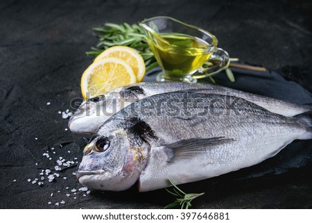 Two ready to cook raw bream fish with herbs, lemon and olive oil on stone slate board over black textured background. Close up - stock photo