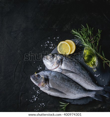 Two ready to cook raw bream fish with herbs, lemon and olive oil on stone slate board over black textured background. With copy space. Top view. Square image.