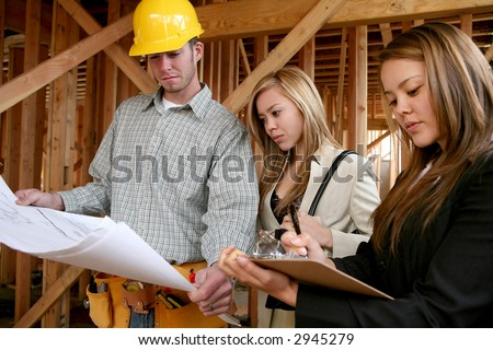 Two real estate agents working with a construction home builder - stock photo
