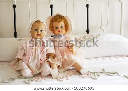 Two real looking antique baby dolls dressed in vintage pink outfits sitting on vintage chanille bedspread on antique iron bed. - stock photo