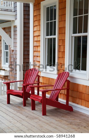 Two red Adirondack chairs on a wood deck against a brown wood shake home - stock photo
