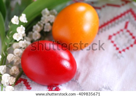 two red and orange easter eggs with may-lily flowers - stock photo