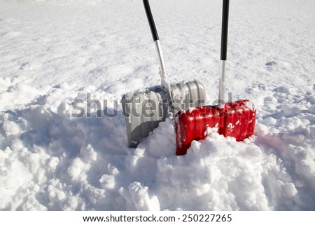 Two, red and silver color, snow shovels for snow removal in deep fresh snow. - stock photo