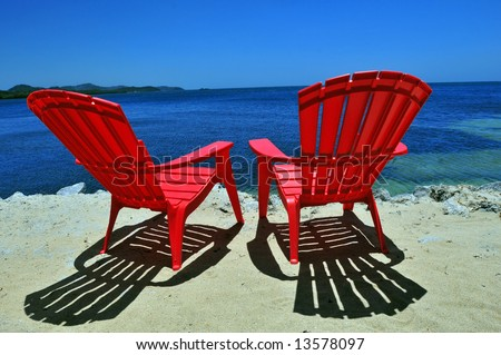 two red beach chairs on white sand with caribbean sea view - stock photo