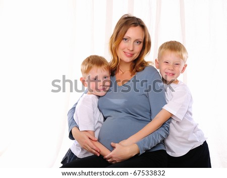 Two red brothers and their pregnant mother spend time together. - stock photo