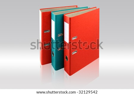 Two red business folders and one green on gray background. - stock photo