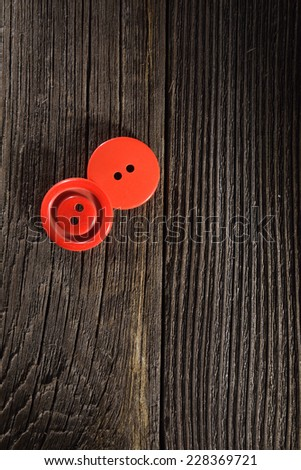 two red buttons on old wooden boards - stock photo