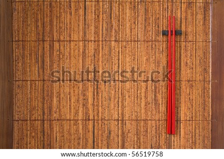 Two red chopsticks on bamboo mat with copy space - stock photo