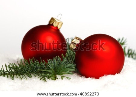 Two red christmas balls, fir branch on snow, isolated on white background - stock photo