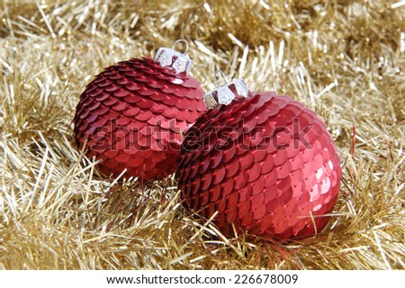 Two red Christmas sequin baubles on golden tinsel. - stock photo