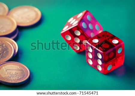 Two red dices with stuck of coins on green background. Vintage. Close-up. - stock photo