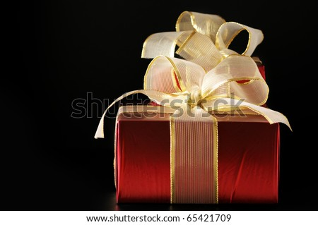 Two red foil gifts with golden bows on black background. - stock photo