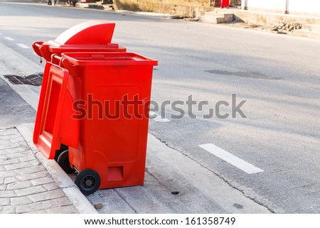 Two red garbage bins put on the street - stock photo