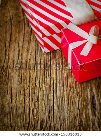 two  red gift boxes on a wooden background/  holidays background with two present boxes