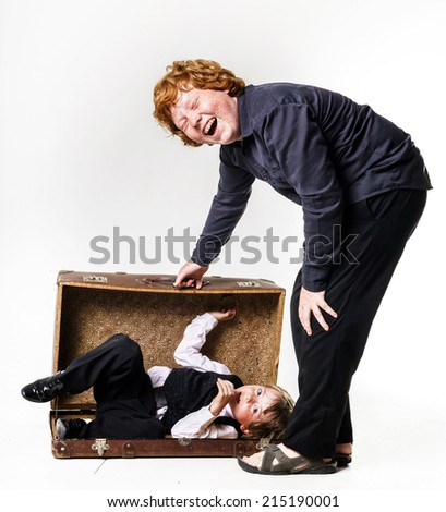 Two red-haired brothers playing with vintage suitcase