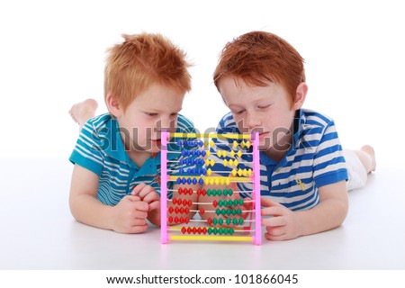 Two red head cheeky boy brothers wearing blue, lying and counting maths with an abacus isolated on white