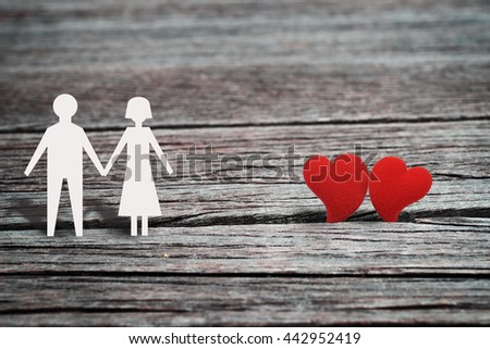 Two red heart shape, symbol of love, with paper character of man and woman holding hand and standing together on wood background,  romantic love concept for Valentine's day season. Vintage style. - stock photo